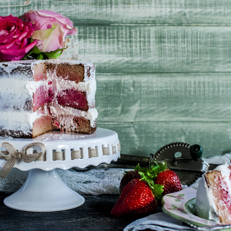 Paleo Strawberry Rose Cake - Layers of freshly sliced strawberries, fresh ground rose petals, whipped coconut cream, finished with a thin layer of buttercream icing. #certifiedpaleo #paleofriendly #paleo